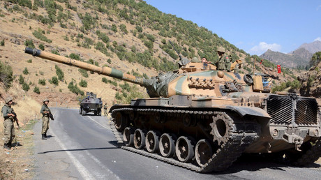 Turkish soldiers in a tank and an armored vehicle patrol on the road to the town of Beytussebab in the southeastern Sirnak province, Turkey. © Stringer