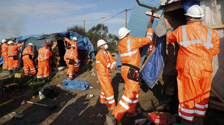 Workmen tear down makeshift shelters on the second day the evacuation of migrants and their transfer to reception centers in France, as part of the dismantlement of the camp called the