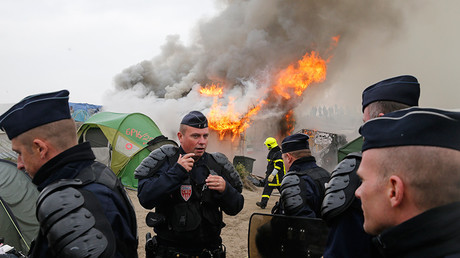 "French police secure the area as firefighters extinguish burning makeshift shelters and tents in the ""Jungle"" in Calais, France, October 26, 2016 © Pascal Rossignol"