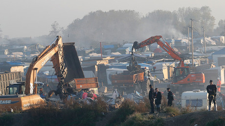 Bulldozers are used to remove debris as workmen tear down makeshift shelters during the dismantlement of the camp called the