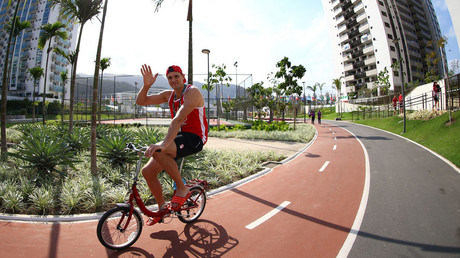An athelete cycles during the Olympic Village media tour. © Jeremy Lee