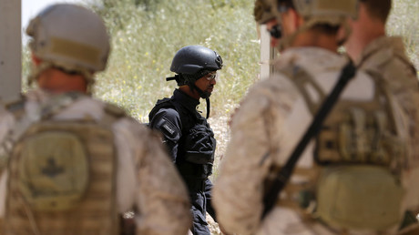 A Saudi Arabian soldier walks next to U.S. soldiers before their mission at the 7th Annual Warrior Competition at the King Abdullah Special Operations Training Center in Amman April 21, 2015. © Muhammad Hamed