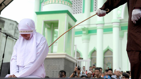 A 20-year old Muslim woman gets caned after being caught in close proximity with her boyfriend in Banda Aceh on October 31, 2016. © Chaideer Mahyuddin