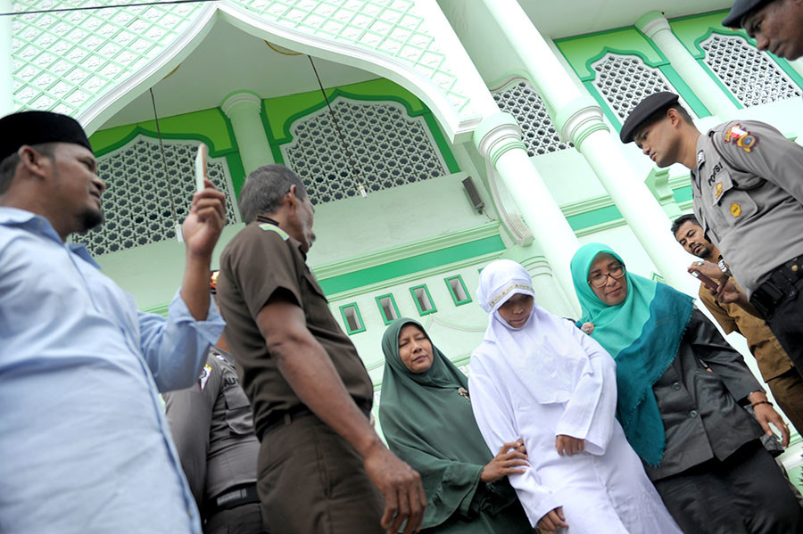 A 20-year old Muslim woman is brought for public caning after being caught in close proximity with her boyfriend in Banda Aceh on October 31, 2016. © Chaideer Mahyuddin