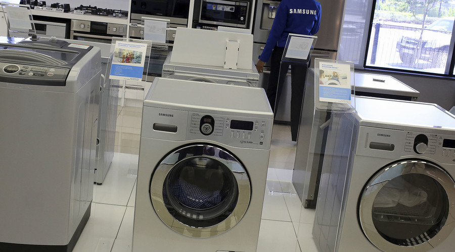 Samsung washing machines are seen as an employee inspects refrigerators at a Samsung display store in Johannesburg
