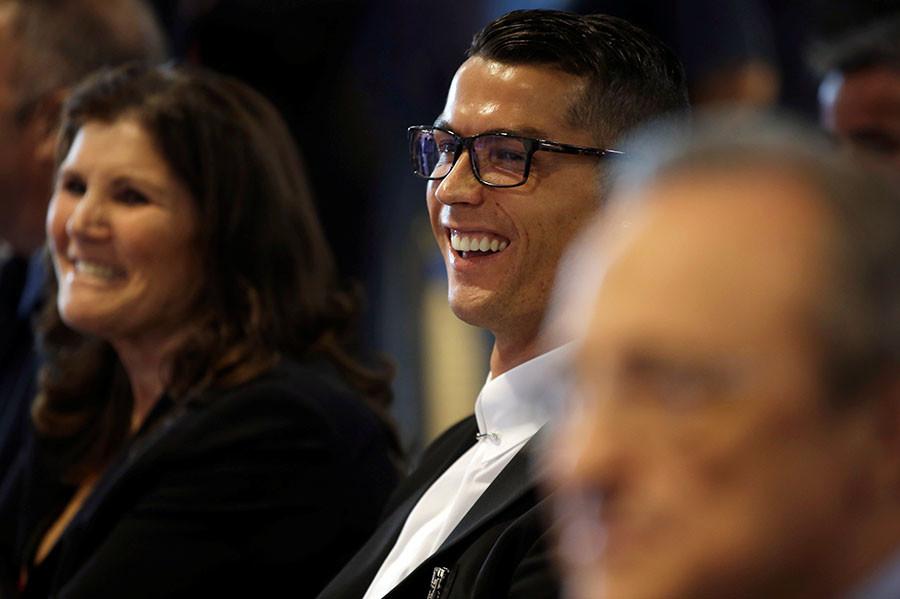Cristiano Ronaldo (C) smiles next to his mother Dolores Aveiro during a ceremony for contract renewal at Santiago Bernabeu ©Susana Vera