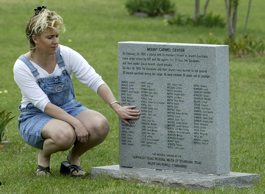 Alana Gonzalez of Berrien Springs, Michigan, touches a memorial stone with the names of all the Branch Davidians that died ten years ago today at their compound, April 19, 2003 at the Mt Carmel compound near Waco, Texas. ©Jason Reed