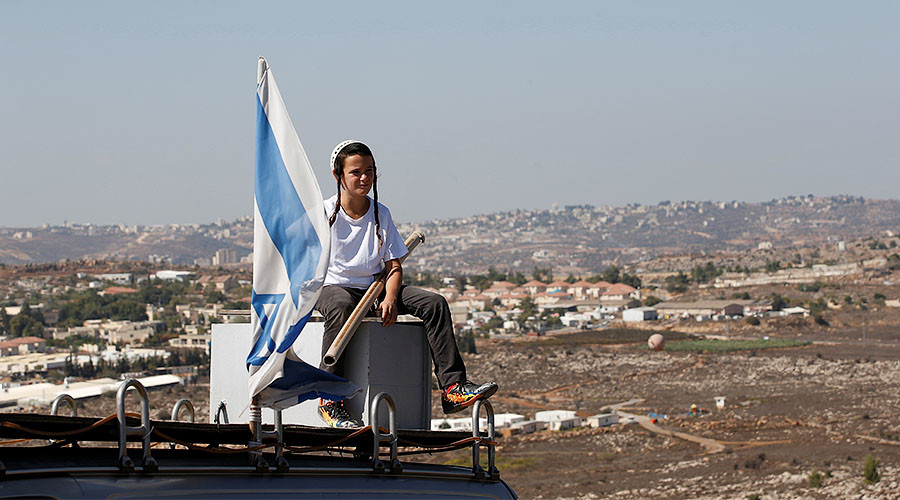 A boy sits near an israeli flag atop the roof of a vehicle at the entrance to the Jewish settler outpost of Amona in the West Bank, October 20, 2016. © Ronen Zvulun