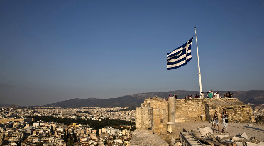 A Greek flag flutters in the wind as tourists visit the archaeological site of the Acropolis hill in Athens, Greece. © Ronen Zvulun