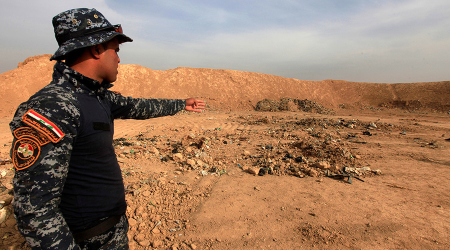 A member of Iraqi security forces gestures towards a mass grave for corpses in the town of Hammam al-Alil which was seized from Islamic State last week, Iraq November 9, 2016 © Alaa Al-Marjani