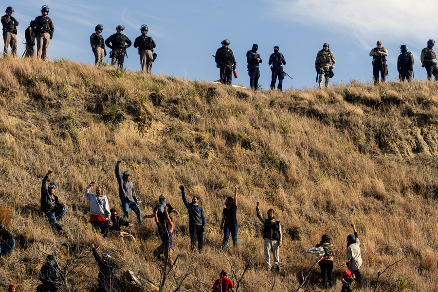 Protesters hold up their arms on a hillside while police stand guard during a protest against the Dakota Access pipeline near the Standing Rock Indian Reservation near Cannon Ball, North Dakota November 6, 2016. © Stephanie Keith