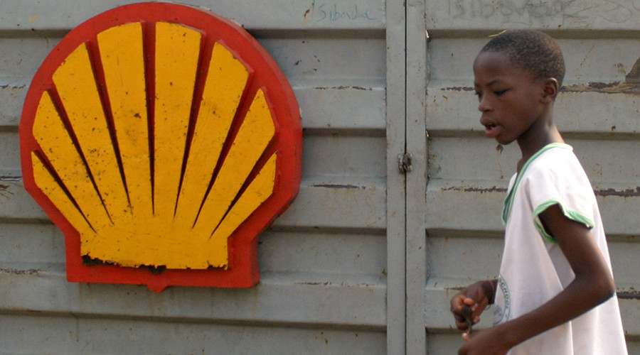 A Nigerian schoolboy walks past the logo of Dutch oil giant Shell near Warri in the volatile Niger-Delta region © George Esiri