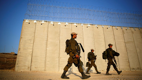 Soldiers walk past the ongoing construction site of Israel's barrier with the West Bank as seen from Havat Ela in southern Israel. © Amir Cohen