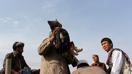 An Afghan man carries the dead body of a child following a NATO coalition airstrike on the outskirts of Kunduz on November 3, 2016. © Bashir Khan Safi