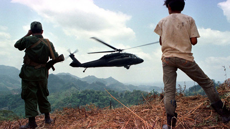 A Nicaraguan soldier and a local boy watch a U.S. helicopter, 