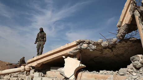 An Syrian Democratic Forces (SDF) fighter stands with his weapon on the rubble of a destroyed building, north of Raqqa city, Syria November 7, 2016. © Rodi Said