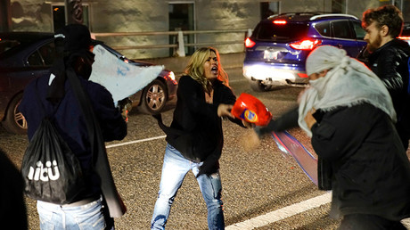 A motorist who was caught in the middle of a riot threatens a demonstrator with detergent during a protest against the election of Republican Donald Trump as President of the United States in Portland, Oregon, U.S. November 10, 2016 © William Gagan