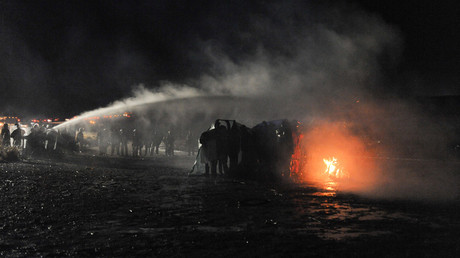 Police use a water cannon to put out a fire started by protesters during a protest against plans to pass the Dakota Access pipeline near the Standing Rock Indian Reservation, near Cannon Ball, North Dakota, U.S. November 20, 2016. © Stephanie Keith