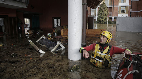 An Italian Red Cross rescuer looks up as he pushes an inflatable dinghy used to evacuate people from their home in Moncalieri, near Turin, on November 25, 2016 because of the floods due to heavy rains. © Marco Bertorello