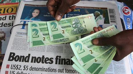 A street vendor poses with new bond notes in the capital Harare, Zimbabwe, November 28, 2016. ©Philimon Bulawayo