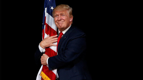 Republican presidential nominee Donald Trump hugs a US flag as he comes onstage to rally with supporters in Tampa, Florida, October 24, 2016. © Jonathan Ernst