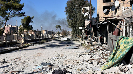 Smoke rises behind a damaged street in Hanano housing district after government forces took control of the area in Aleppo, Syria, November 27, 2016. © SANA