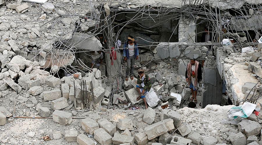 A man sits near others amidst rubble of a building destroyed by Saudi-led air strikes in the northwestern city of Amran, Yemen