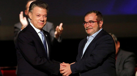 Colombia's President Juan Manuel Santos and Marxist FARC rebel leader Rodrigo Londono, known as Timochenko, shake hands after signing a peace accord in Bogota, Colombia November 24, 2016 © Jaime Saldarriaga