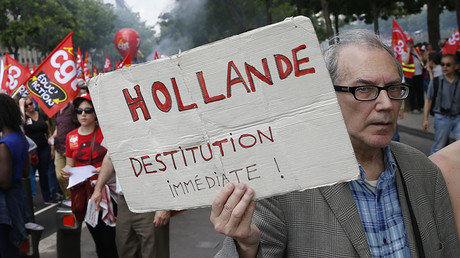 A man holds a placard which reads,