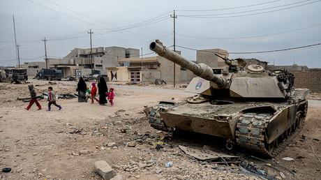 A family walks past a destroyed M-1 Abrhams tank in Gogjali.  © Gabriel Romero / Global Look Press via ZUMA Press