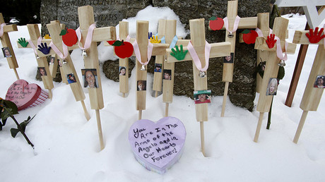 Crosses are seen in the snow as part of a makeshift memorial at Edmond Town Hall in Newtown, approximately three weeks after a gunman shot dead 20 students and six adults at Sandy Hook Elementary, in Newtown, Connecticut, January 2, 2013. © Carlo Allegri