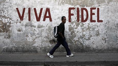 "A man walks past a graffitti that reads ""Long live Fidel"" in Santiago de Cuba © Claudia Daut"