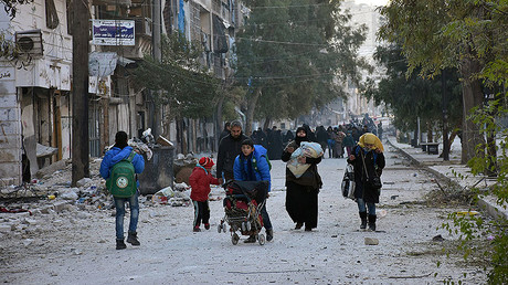 People, who evacuated the eastern districts of Aleppo, carry their belongings as they arrive in a government held area of Aleppo, Syria, December 7, 2016. © SANA / Handout via Reuters
