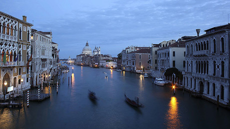 Gondoliers row in an empty Grand Canal in Venice. © Manuel Silvestri