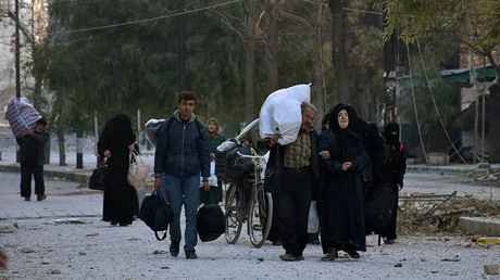 People, who evacuated the eastern districts of Aleppo, carry their belongings as they arrive in a government held area of Aleppo, Syria, in this handout picture provided by SANA on December 7, 2016. ©SANA