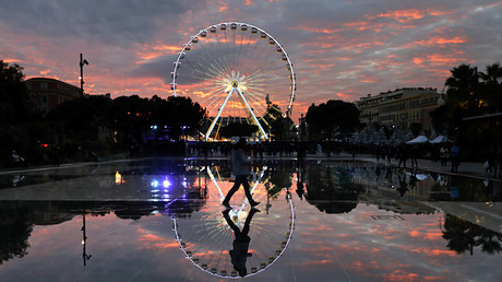 A man is reflected in the water of a fountain as he walks by a Ferris wheel as part of Christmas holiday season illuminations in Nice, France, December 5, 2016 © Eric Gaillard