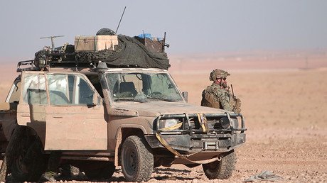 A U.S. fighter stands near a military vehicle, north of Raqqa city, Syria © Rodi Said