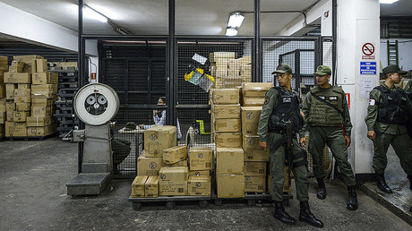 Members of the Venezuelan national guard stand next to boxes full of confiscated toys in a warehouse in Caracas on December 9, 2016. © Federico Parra
