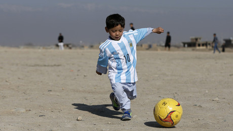 FILE PHOTO Five year-old Murtaza Ahmadi, an Afghan Lionel Messi fan, wears a shirt signed by Barcelona star Lionel Messi as he plays football at the open area in Kabul, Afghanistan © Omar Sobhani
