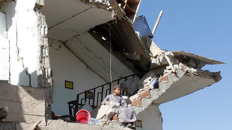 FILE PHOTO: A boy sits on the wreckage of a house destroyed by a Saudi-led air strike on the outskirts of Sanaa, Yemen © Mohamed al-Sayaghi