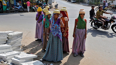 Sarta Kalara (C), a construction worker, stands among other female workers in Ahmedabad, India, April 20, 2016. © Amit Dave