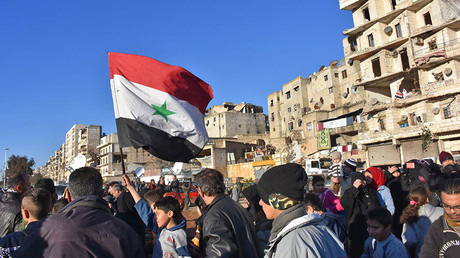 A young boy waves the Syrian flag as residents in a government-held area of Aleppo gather in the street during an evacuation operation of rebel fighters and their families from rebel-held neighbourhoods in Syria's northern embattled city on December 15, 2016. ©Youssef Karwashan