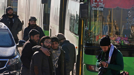 Men react as they stand outside buses evacuating people from a rebel-held sector of eastern Aleppo, Syria December 15, 2016
