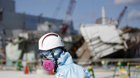A Tokyo Electric Power Co. (TEPCO) employee, wearing a protective suit and a mask, walks in front of the No. 1 reactor building at TEPCO's tsunami-crippled Fukushima Daiichi nuclear power plant in Okuma town, Fukushima prefecture, Japan February 10, 2016. © Toru Hanai