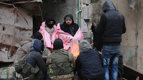 Rebel fighters warm by a fire in a rebel-held sector of eastern Aleppo, Syria December 18, 2016 © Abdalrhman Ismail