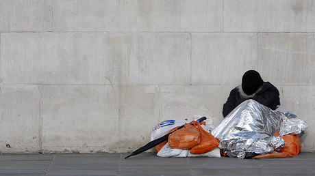 A homeless man sleeps under a foil blanket in Trafalgar Square in London. © Luke MacGregor