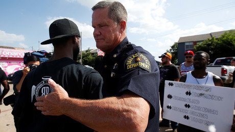 FILE PHOTO: A Dallas police officer hugs a man following a prayer circle after a Black Lives Matter protest following the multiple police shootings in Dallas, Texas, U.S., July 10, 2016. © Danny Moloshok