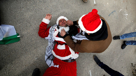 A man tends to a Palestinian protester, dressed as Santa Claus, after inhaling tear gas fired by Israeli troops during clashes in the West Bank city of Bethlehem, December 23, 2016. © Mussa Qawasma