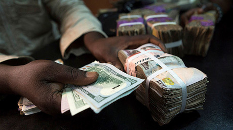 A trader changes dollars with naira at a currency exchange store in Lagos, Nigeria. © Joe Penney