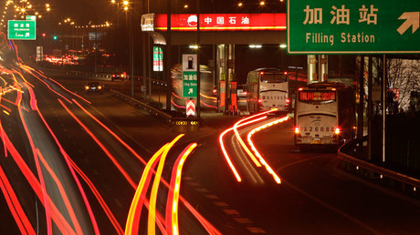 Cars drive into a Petrol China gas station, as other vehicles drive past on the Beijing-Tibet expressway in Beijing © Soo Hoo Zheyang